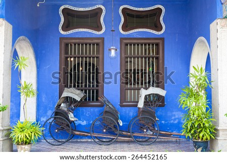 Georgetown Malaysia 04 August 2014 Old rickshaw tricycle near Fatt Tze Mansion or Blue Mansion famous oriental historical building in Georgetown Penang Malaysia on 04 August 2014
