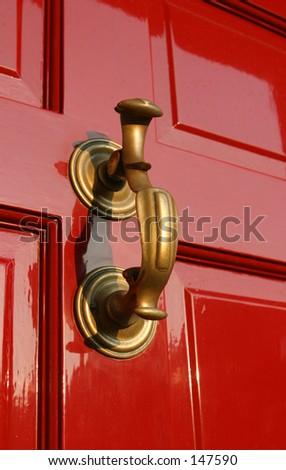 Georgian Door Knocker on burgundy paneled wooden door.