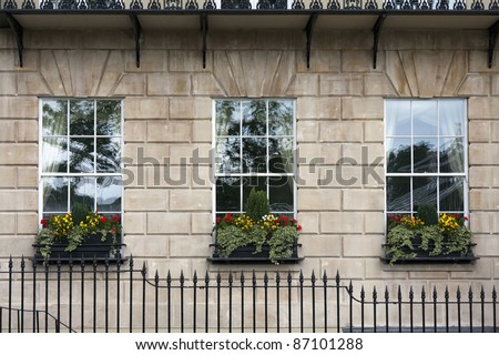 Georgian window triptych. Detail of windows with windowboxes and wrought iron railings on facade of Georgian building.