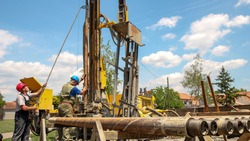 Geothermal Drillers at Work. Drilling geothermal well for a residential geothermal heat pump. Geothermal water well drilling equipment. Workers lifting a drill pipe on a drilling rig.