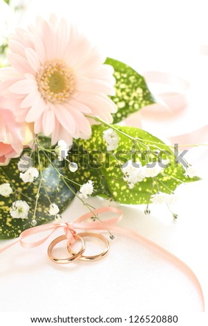 Gerbara bouquet and golden wedding ring with ribbon