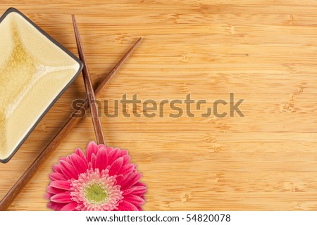 Gerber Daisy, Chopsticks and Dish on a Bamboo Background with Copy Space.
