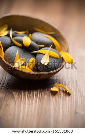Gerbera flower petals and spa stones, wooden background.