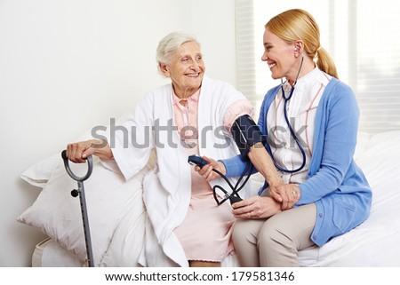 Geriatric nurse measuring blood pressure of senior citizen woman in nursing home