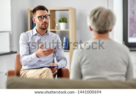 geriatric psychology, mental therapy and old age concept - psychologist talking to senior woman patient at psychotherapy session #1441000694
