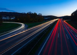 """German Autobahn """"A1"""" in Hagen-West junction at dusk with light traces of passing fast cars and blue evening sky. Long time exposure from a bridge above the six lane highway and white and red lights."""