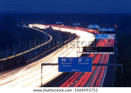 German  autobahn at night. Blue destination signs and light trails of moving cars.
