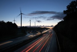 German Autobahn leading past wind turbines towards power plant at sunrise with light trails and motion lblur of the moving cars symbolizing energy and mobility revolution