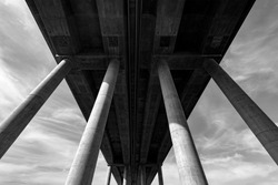 """German """"Autobahn"""" or Motorway Bridge over the river Lahn near Limburg in Hessen Germany with tall concrete pylons from frog perspective black and white on a sunny day"""