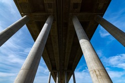 """German """"Autobahn"""" or Motorway Bridge over the river Lahn near Limburg in Hessen Germany with tall concrete pylons from frog perspective on a sunny blue sky day"""