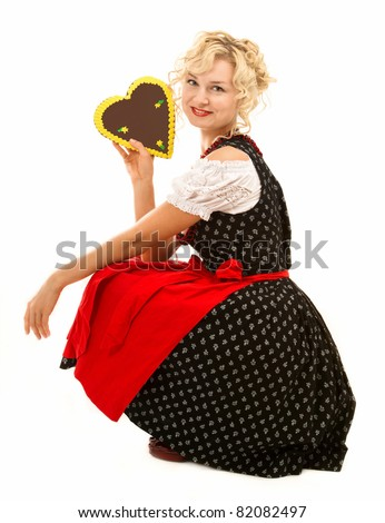 german bavarian girl in dirndl with typical octoberfest cookie