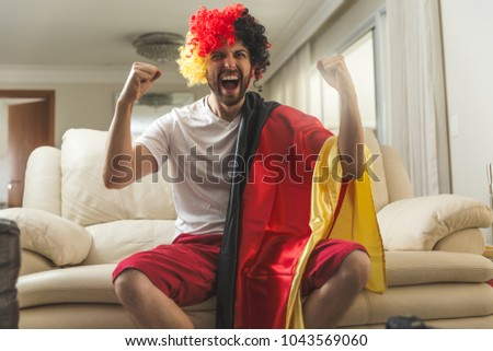 German fan watching a soccer match at home