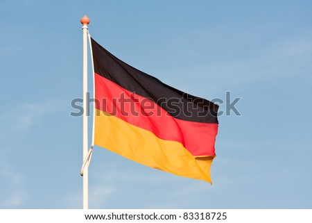 German flag blowing in the wind against a blue sky - stock photo