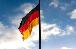 German Flag in black-red-gold colors on a sunny day in german capital Berlin near the Reichtstag Building is the national Symbol of the Bundesrepublik Deutschland
