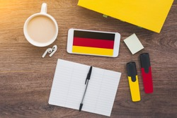 German flag, notebook, textbook, smartphone and wireless headphones on a wooden desktop, foreign language learning concept