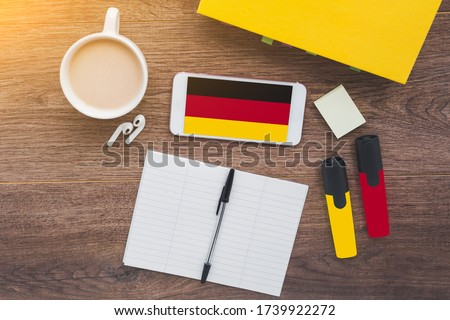 German flag, notebook, textbook, smartphone and wireless headphones on a wooden desktop, foreign language learning concept Stockfoto ©