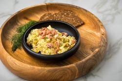 German Friesland north sea shrimps with scrambled eggs, whole grain bread and dill in wooden bowl on marble background