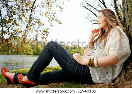 German girl sitting in the park.