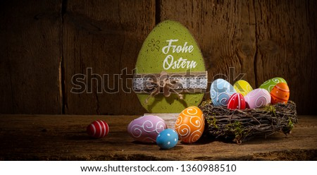 German greetings Frohe Ostern ( english translation happy easter ) Colorful painted eggs in birds nest basket on rustic wooden old  greeting card panorama background #1360988510