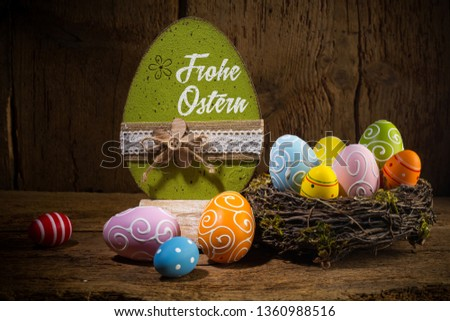 German greetings Frohe Ostern ( english translation happy easter ) Colorful painted eggs in birds nest basket on rustic wooden old  greeting card background #1360988516