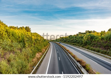 german highway in early morning light, one side empty #1192202497