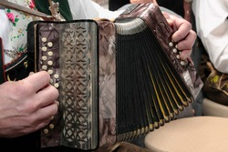 German man's hands playing a traditional accordion