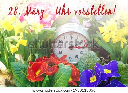German: March 28, Change clock, alarm clock with spring flowers Stock fotó ©