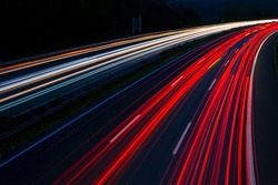 """German Motorway called """"Sauerlandlinie"""" with six curved lanes at blue hour after sunset near Hagen Westphalia with colorful light traces of passing cars and trucks"""