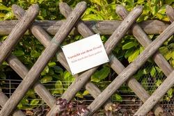 German sign on a fence with plants, outdoor. Vorsicht vor dem Hund. Nicht durch den Zaun greifen - Beware of the Dog. Do not grab through the fence