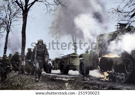 German soldiers passing burning U.S. equipment in the beginning of the Battle of the Bulge. Dec. 16-22, 1944. Still from a captured German film with color added later. B&W Photo with oil color.