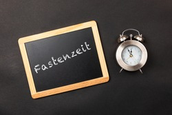 german text fastenzeit, in english fasting time with clock and black background