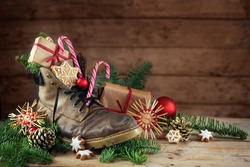 German tradition to put the shoes in front of the door on Nicholas or Nikolaus day at 6th December to get them filled with treats, old hiking boot, rustic wooden background, copy space, selected focus