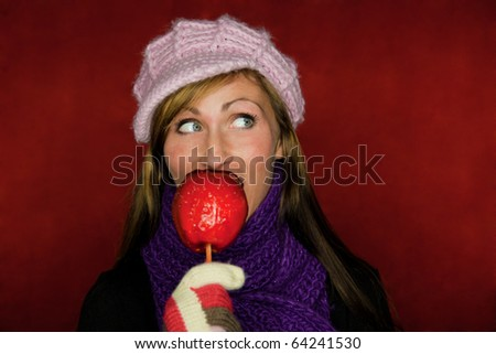German traditional christmas market girl eating red taffy apple - stock photo