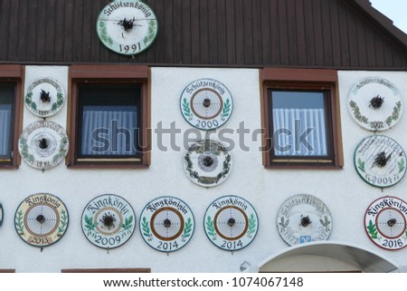 German traditions: Trophies of the champion marksman, the shooting king of a village - Shooting targets from previous years on the wall of the champions house #1074067148