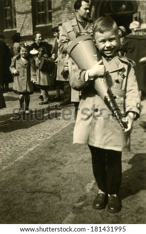 GERMANY -  April 1, 1957: An antique photo of boy in a light raincoat posing with a gift in hand on the background of people on the street
