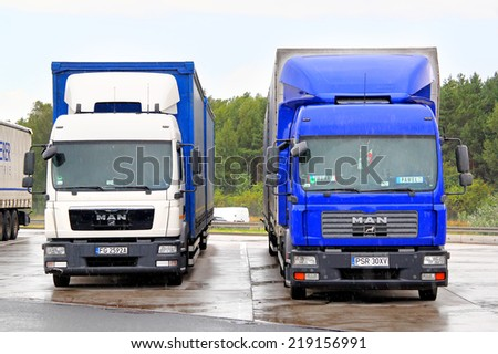 GERMANY - AUGUST 14, 2014: White and blue trucks MAN TGM at the interurban road,
