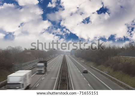 "germany "" autobahn "" the german highway..image taken on a cloudy day with some fog. image with motion blur . - stock photo"