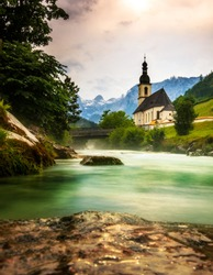 Germany, Bavaria, Berchtesgaden, church at the river with the Alps in the background. Long exposure deeply photographed
