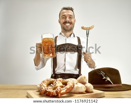 Germany, Bavaria, Upper Bavaria. The young happy smiling man with beer dressed in traditional Austrian or Bavarian costume holding mug of beer at pub or studio. The celebration, oktoberfest, festival ストックフォト ©