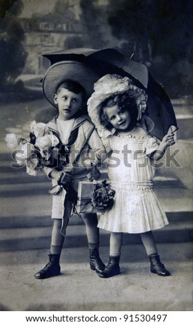 GERMANY - CIRCA 1909: Postcard printed in the Germany shows boy and girl under an umbrella, circa 1909