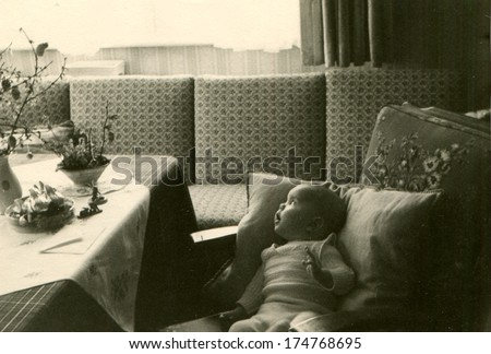 GERMANY -  CIRCA 1950s: An antique photo shows baby lying on pillows on a sofa near the table with a bouquet of flowers and looks aside window