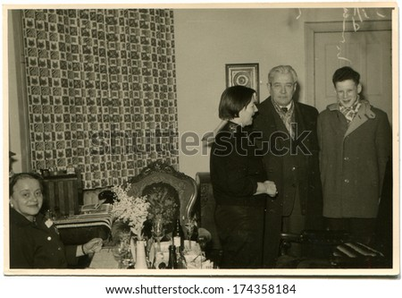 GERMANY -  CIRCA 1960s: An antique photo shows young woman greets guests who came to the home celebration