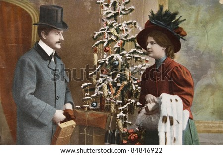 GERMANY - CIRCA 1915: Vintage christmas card printed in Germany in 1915 with loving couple beside a christmas tree with presents, circa 1915.