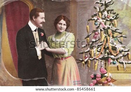 GERMANY- CIRCA 1910: Vintage christmas card with weathered edges printed in Germany in 1915 with loving couple beside a christmas tree  , circa 1910.