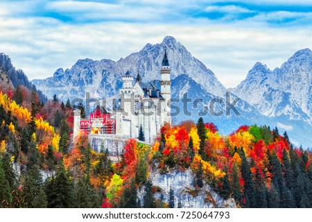 Germany. Classical view on Neuschwanstein castle begirt colorful fall forest in Bavaria land. Beautiful autumn scenery. Neuschwanstein castle is famous and very popular travel destination in Europe. #725064793