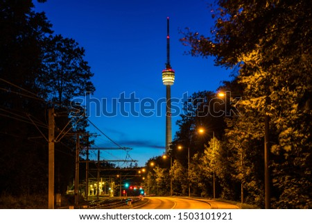 Germany, Empty street alongside railway leading to famous television tower of stuttgart city, called fernsehturm by night in magical twilight atmosphere