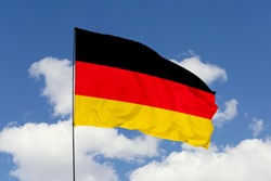 Germany flag isolated on the blue sky with clipping path. close up waving flag of Germany. flag symbols of Germany.