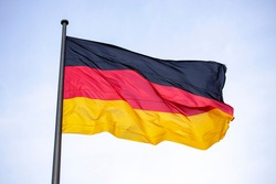 Germany flag waving in the wind close-up against a blue sky