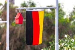 Germany flag with a small house on a flag pole. Germany home concept.