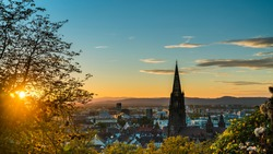 Germany, Freiburg im Breisgau, Magical orange sunset sky and sunrays behind skyline of the beautiful city and muenster